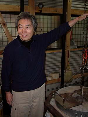 Hosokawa Morihiro in front of Raku Kiln showing flame height
